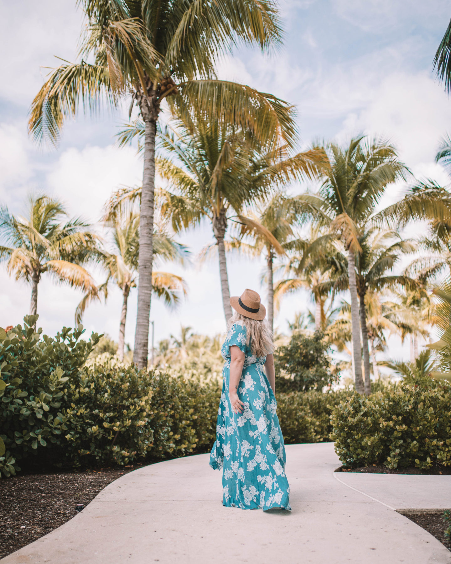 woman wearing blue flowy dress, standing on sidewalk, looking up at palm trees