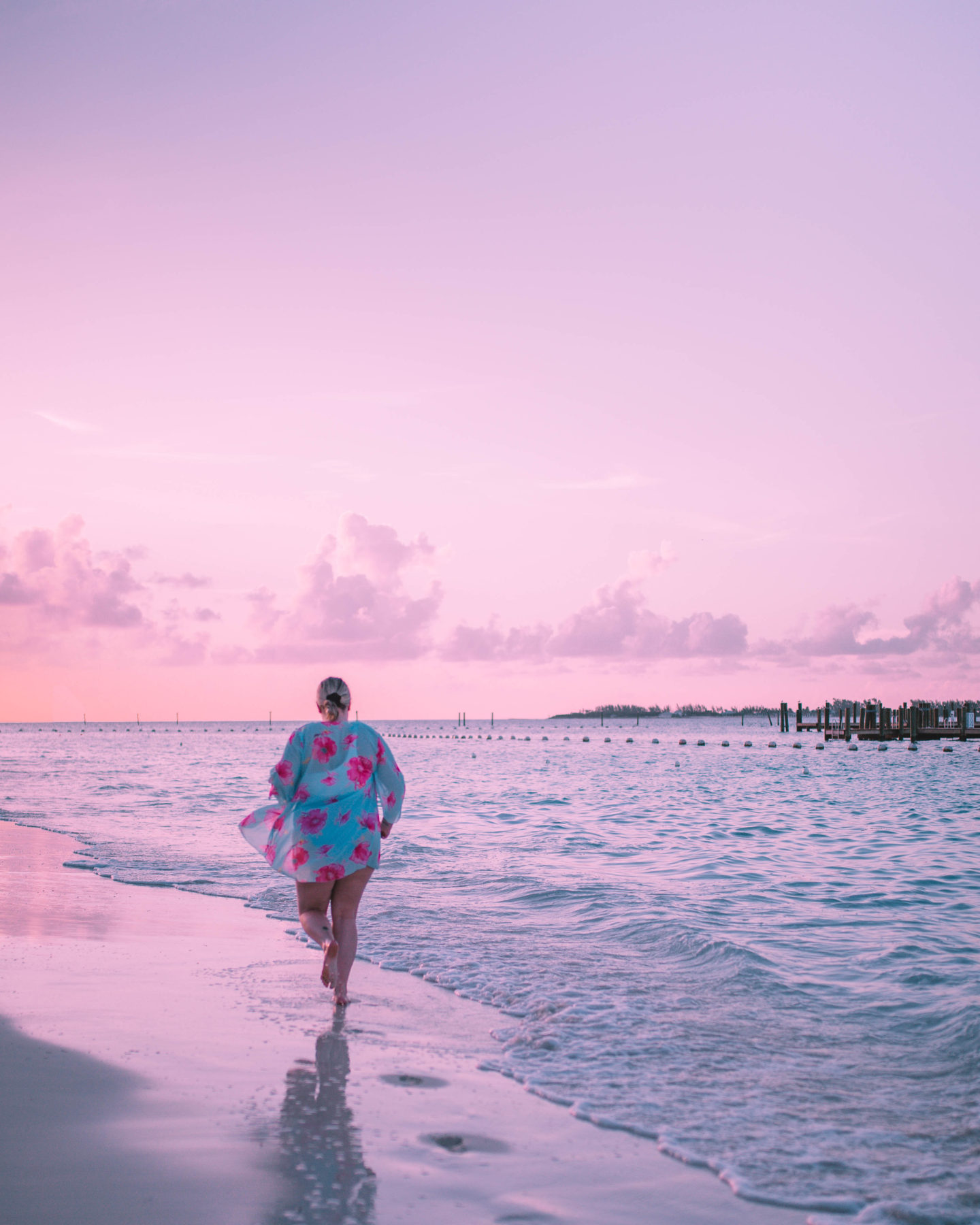 woman running off into sunset with cotton candy skies