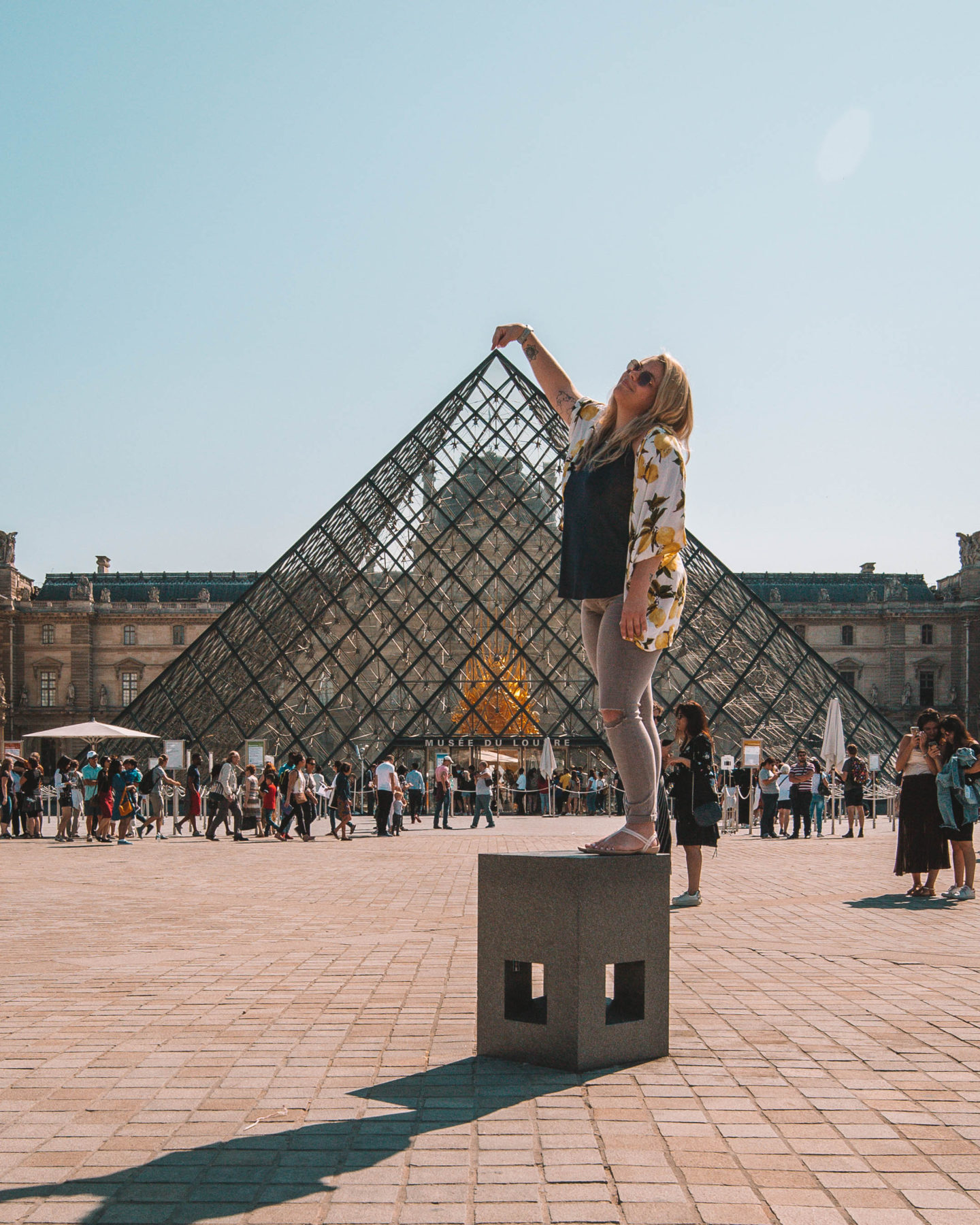 woman touching the top of the louvre pyramid in paris france