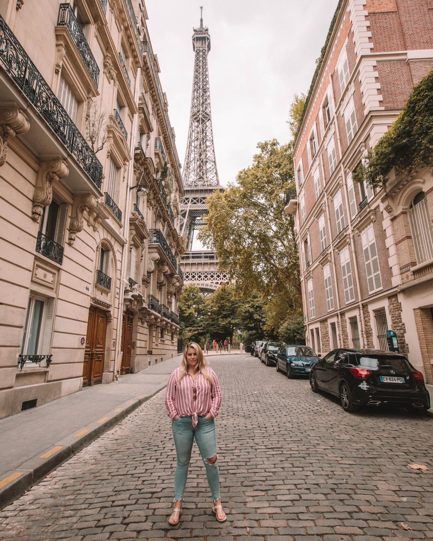 woman standing on cobblestone street in neighborhood overlooking the eiffel tower in paris france