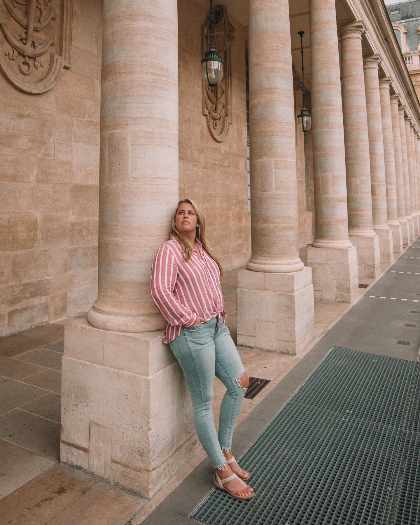 woman leaning against building