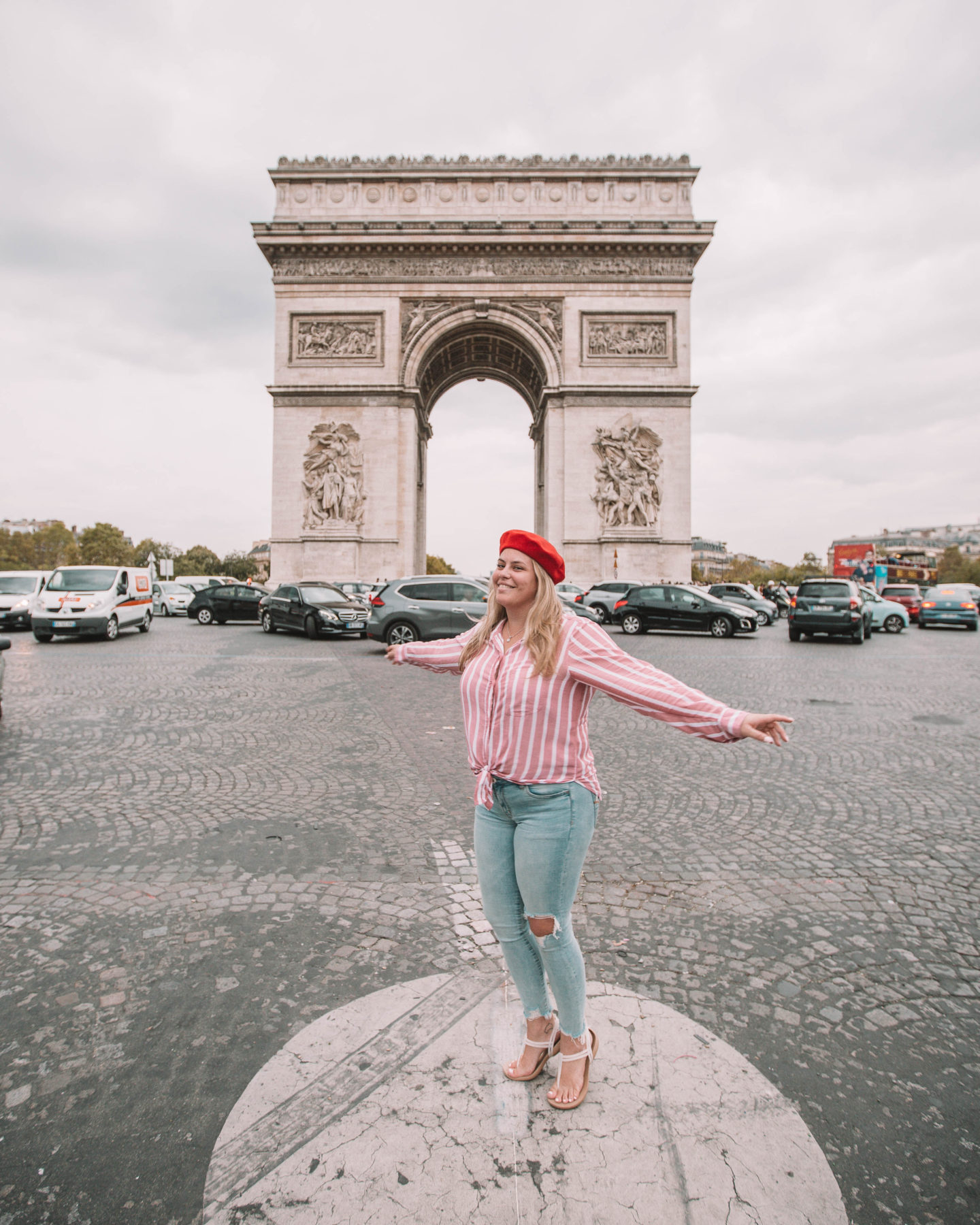 woman wearing red beret in front of the arc de triomphe in paris france