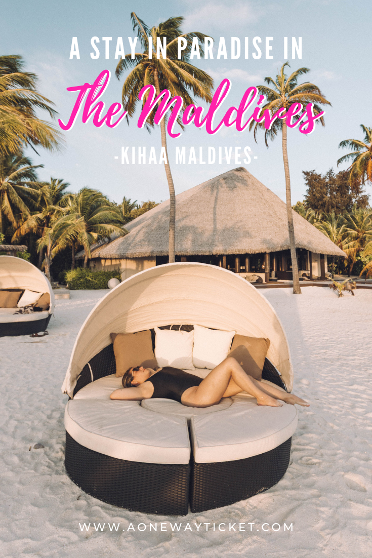 woman laying on a lounger on white sand beach in the maldives surrounded by palm trees