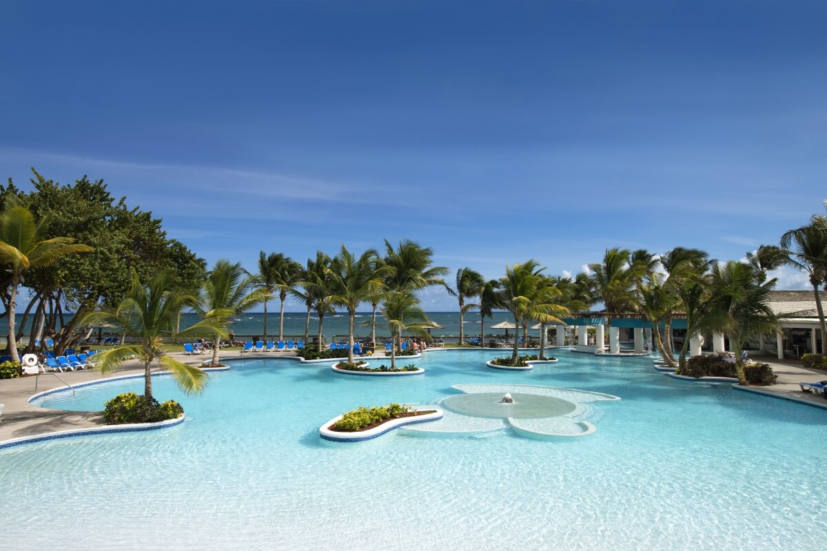 large pool with the beach and ocean in the background at coconut bay beach resort st lucia