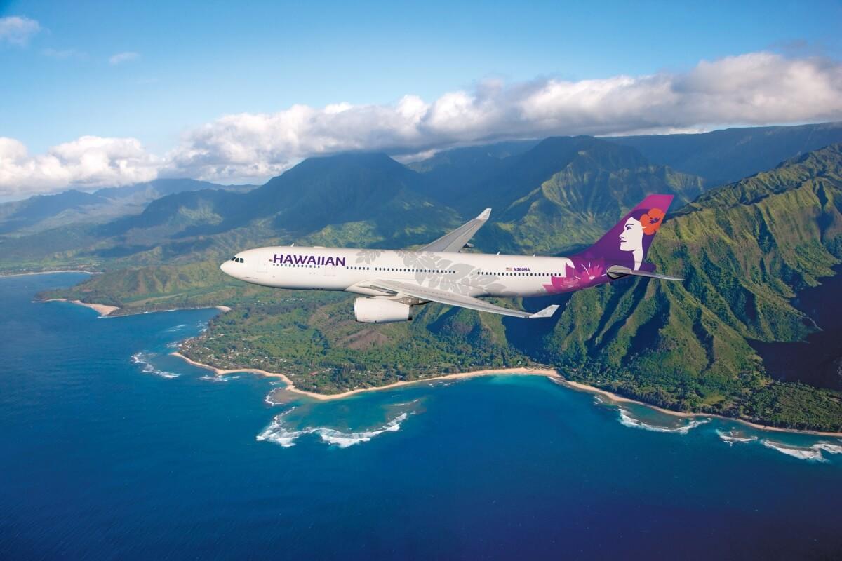 hawaiian airlines plane flying over stunning hawaii backdrop
