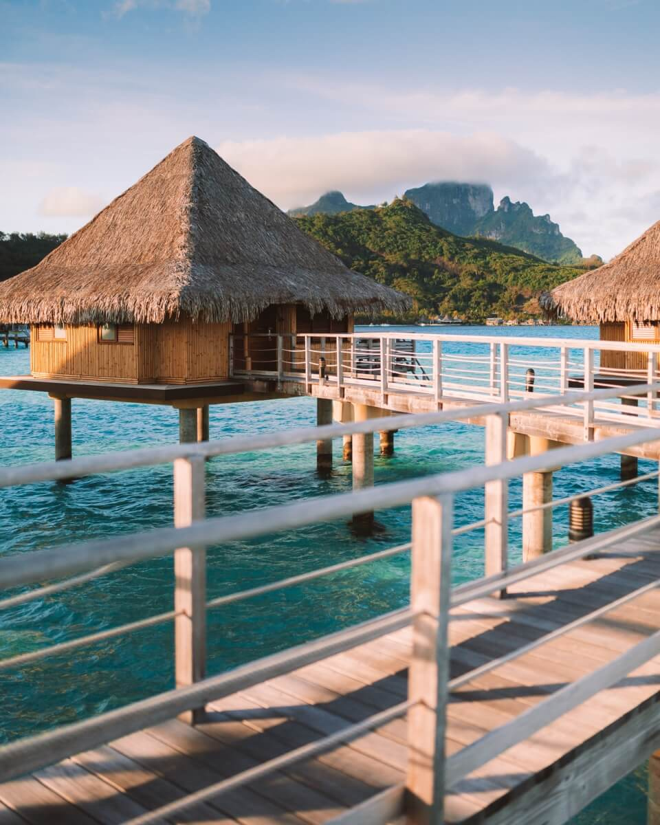 overwater bungalow at intercontinental bora bora le moana resort with walkway framing the shot and bora bora's famous mount otemanu in the backgroundbora bora vs moorea