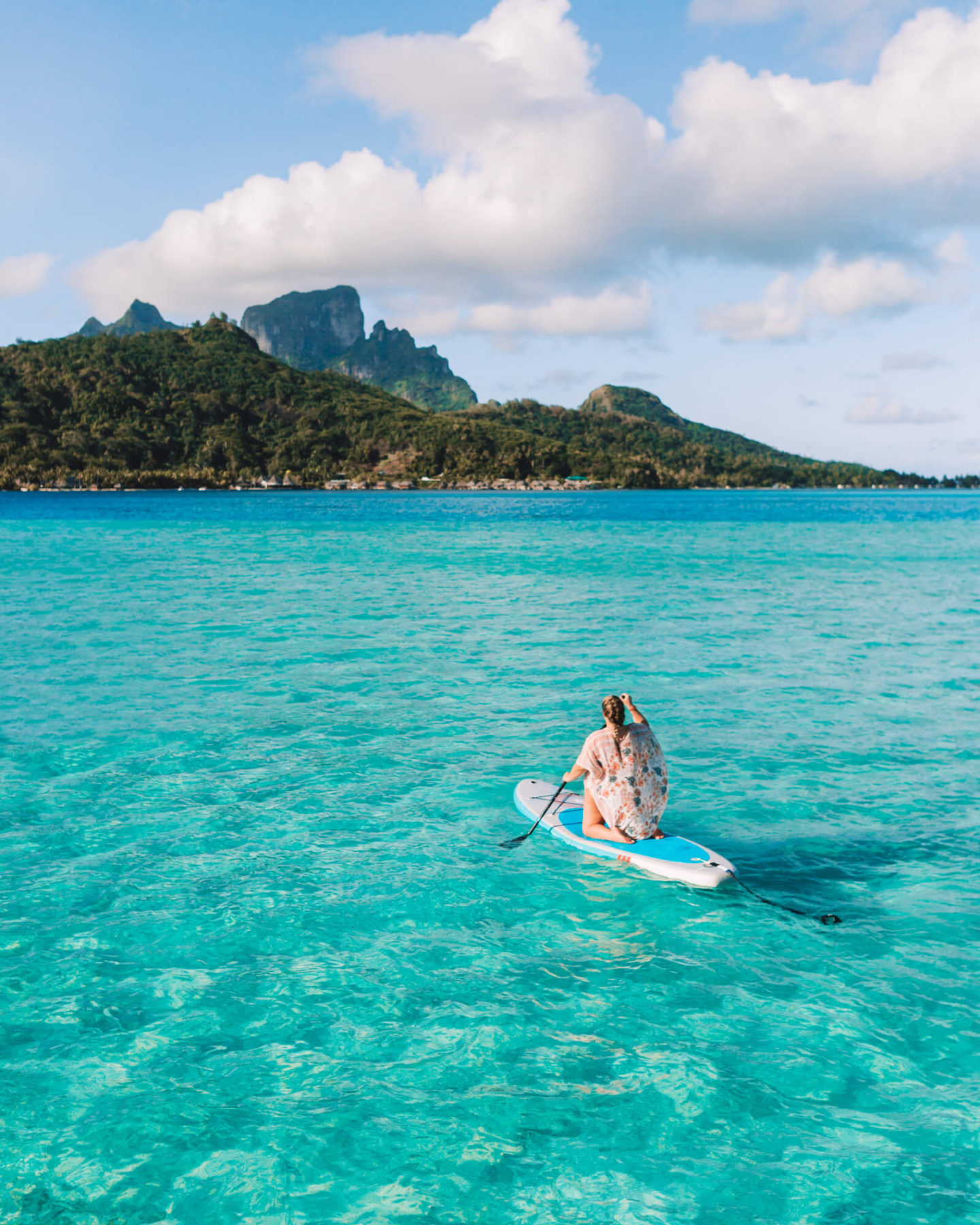 woman paddle boarding while kneeling in bora bora at the intercontinental bora bora le moana in front of bora bora's famous mount otemanu