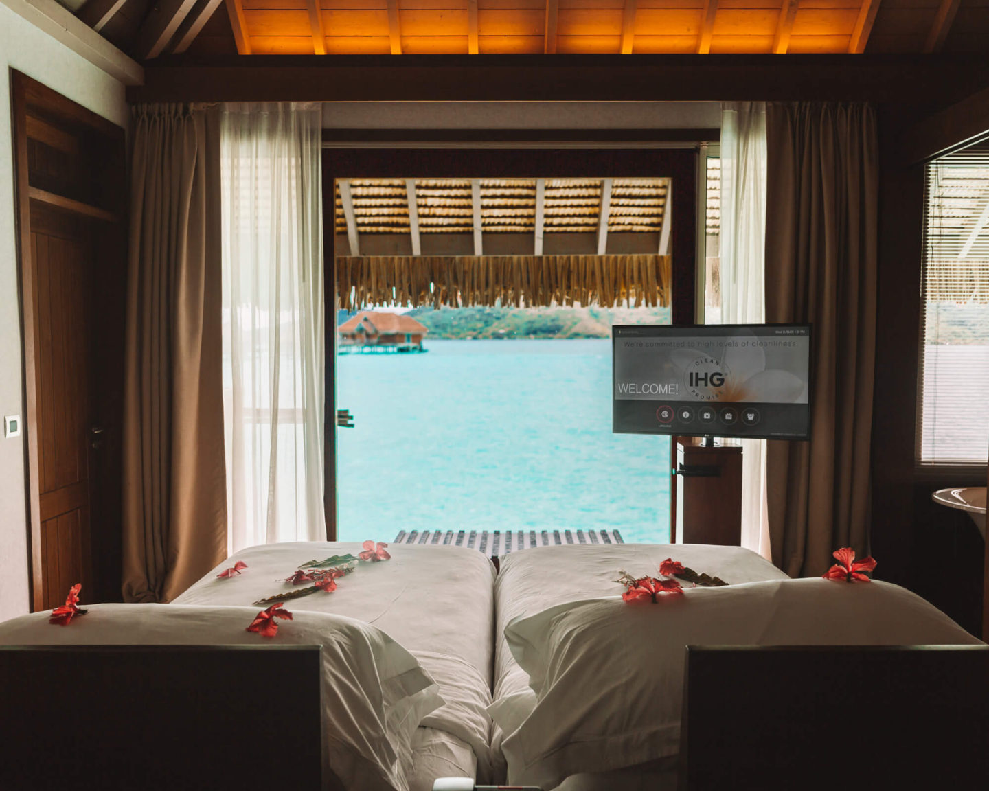 floor to ceiling window with turquoise water view in overwater bungalow at intercontinental thalasso in bora bora