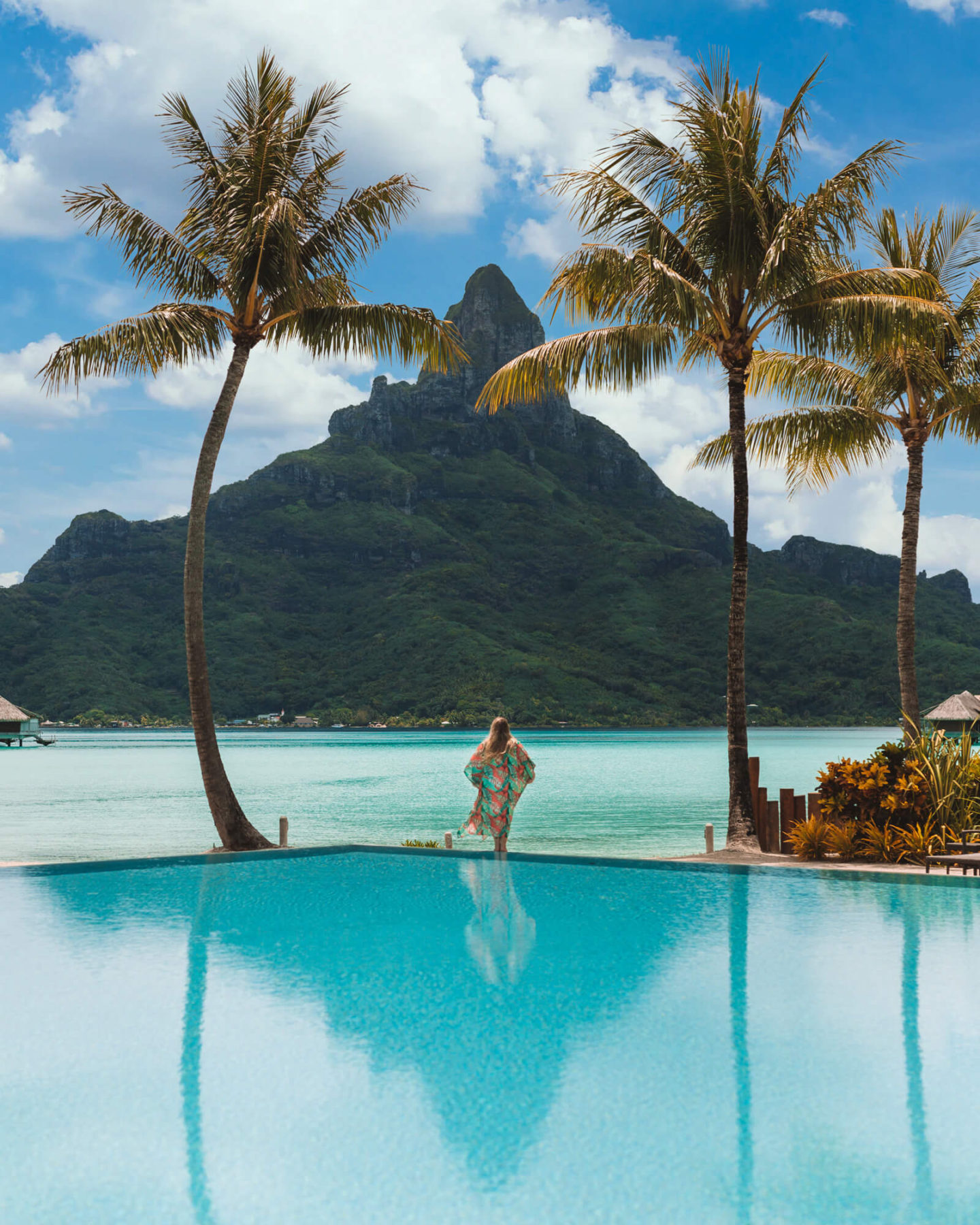 woman standing on edge of pool surrounded by two palm trees that frame mount otemanu at intercontinental thalasso in bora bora
