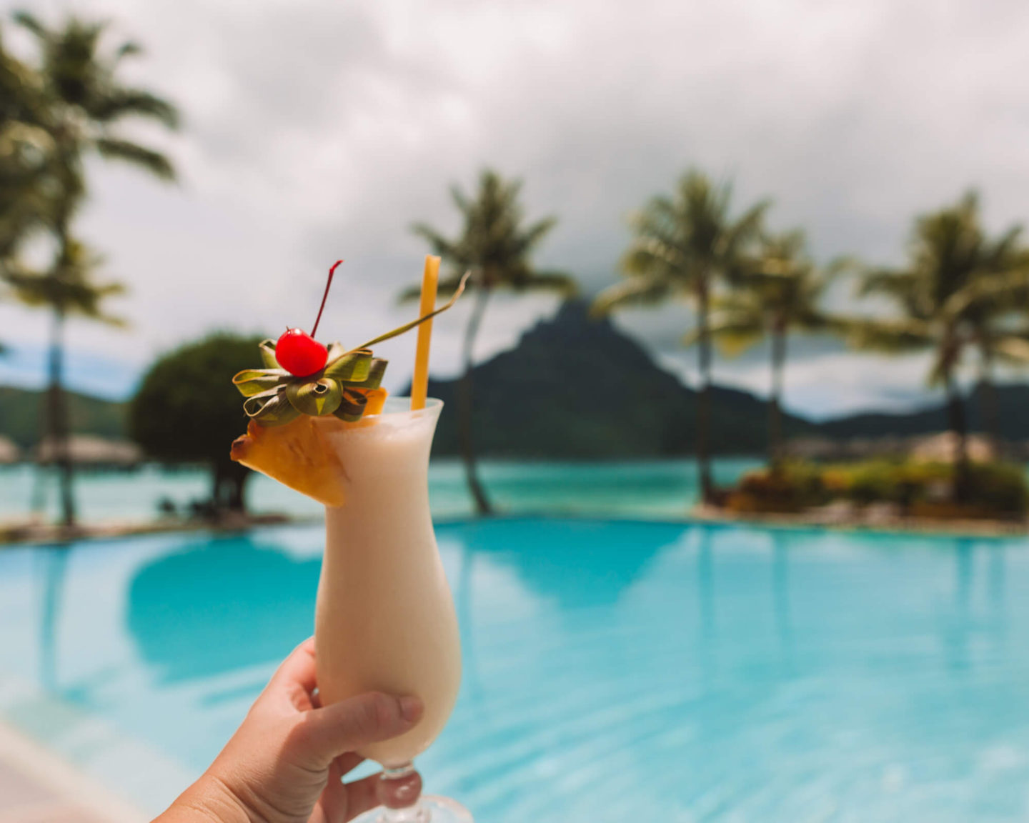 view of mount otemanu in bora bora with woman holding up fruity drink with garnish