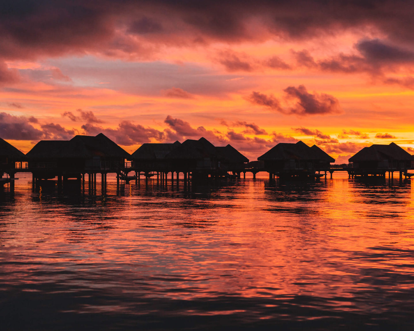 colorful sunset with overwater bungalows in bora bora at intercontinental thalasso