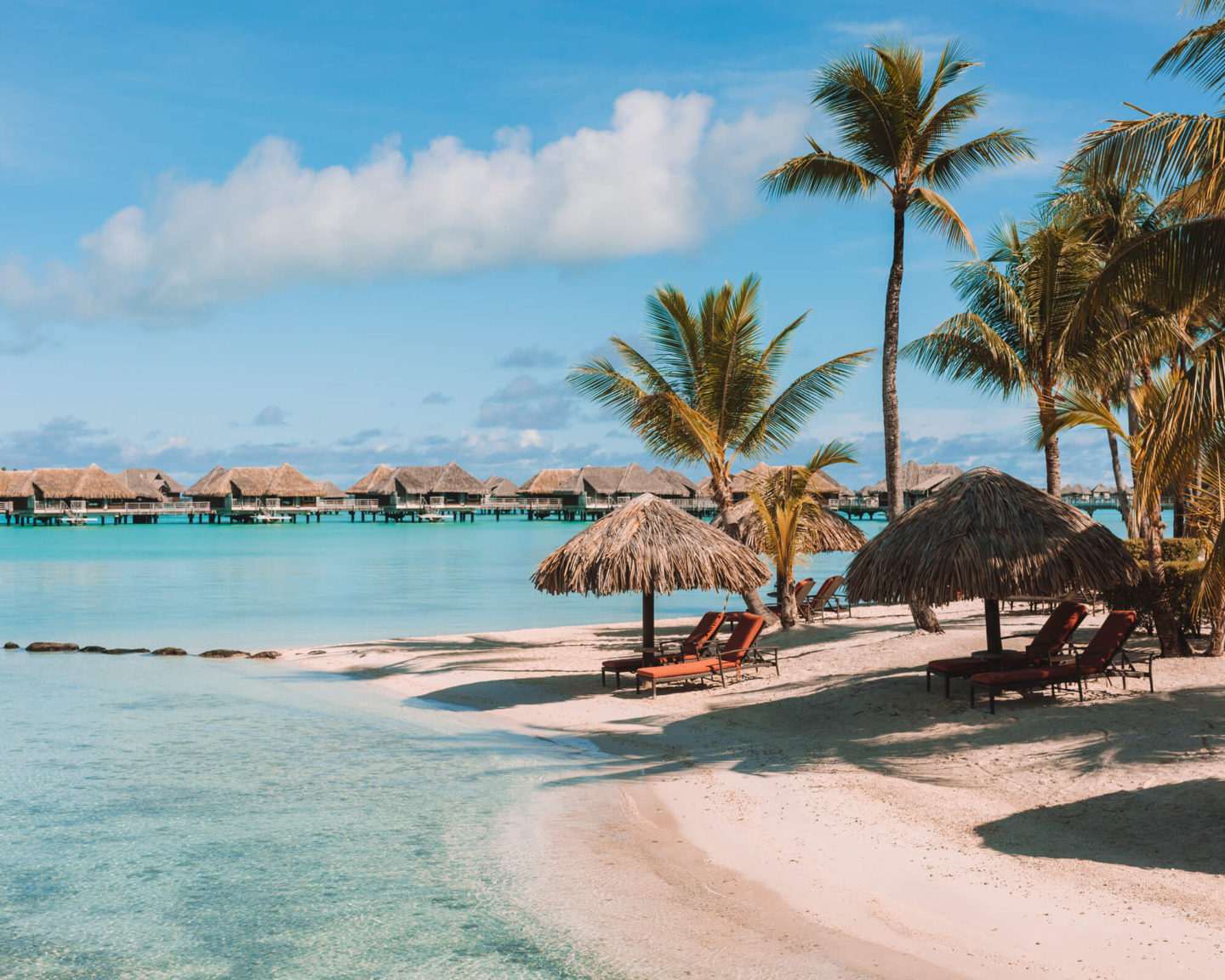 white sand beach with lounge chairs and huts surrounded by palm trees with overwater bungalows in the backdrop intercontinental thalasso bora bora