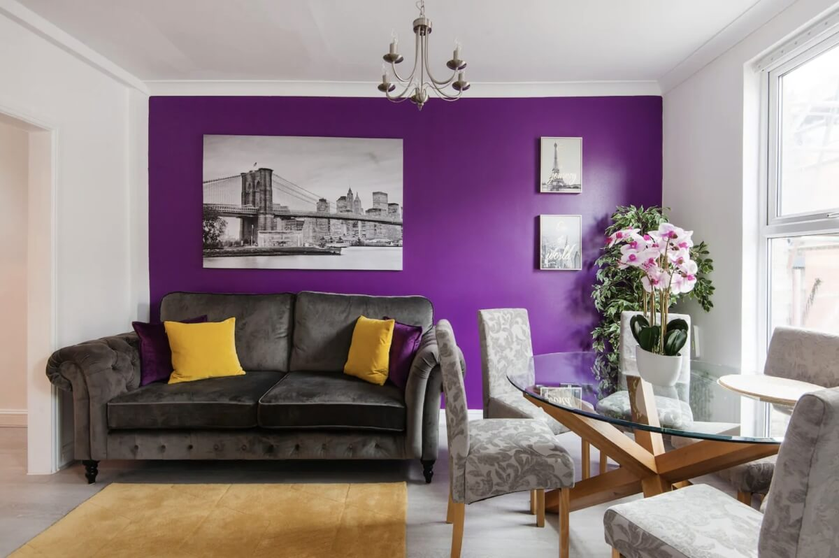 airbnbs in london with purple accent wall and dark furniture with yellow and purple accent pillows