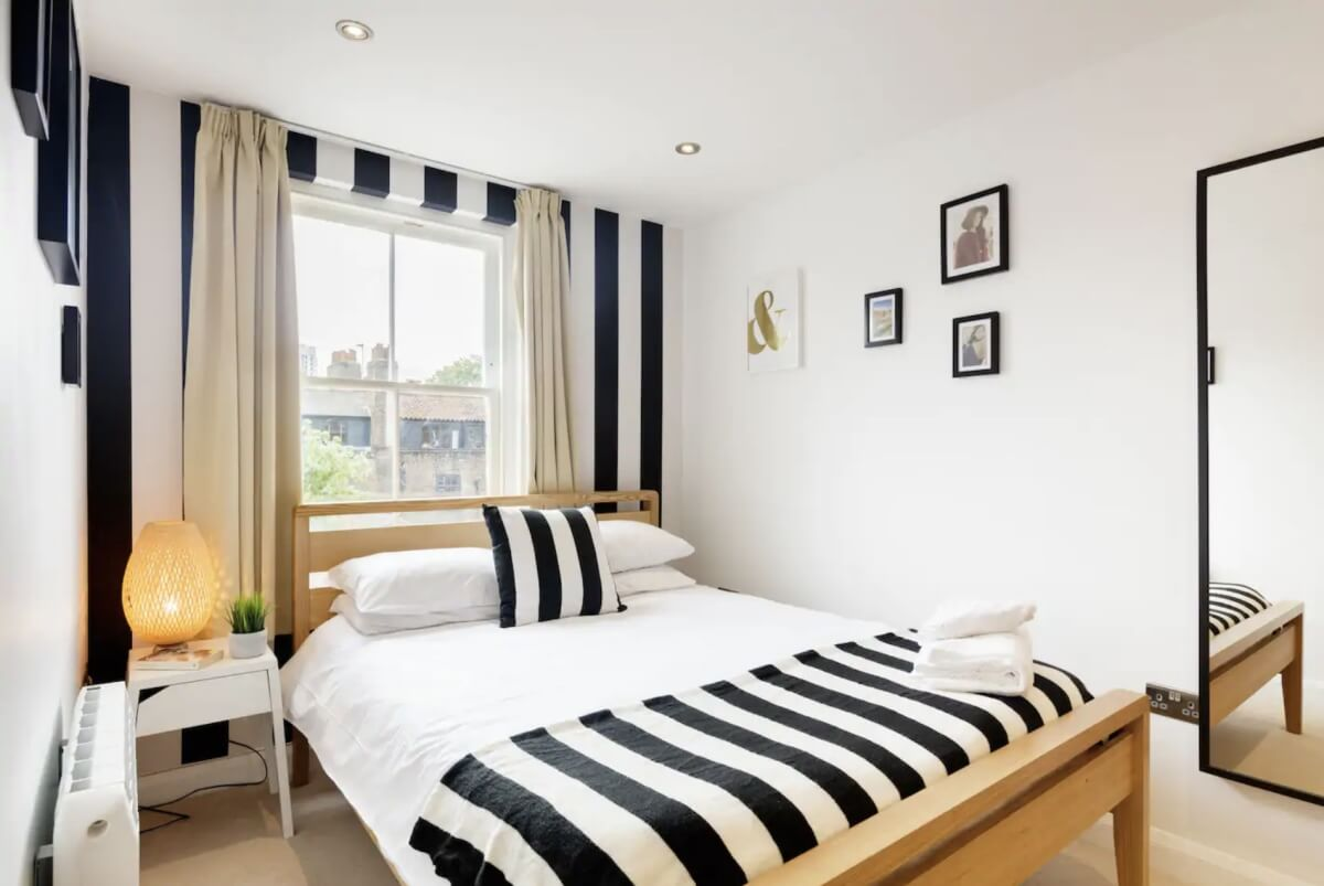london airbnb with black and white stripe accents on the wall and the bed
