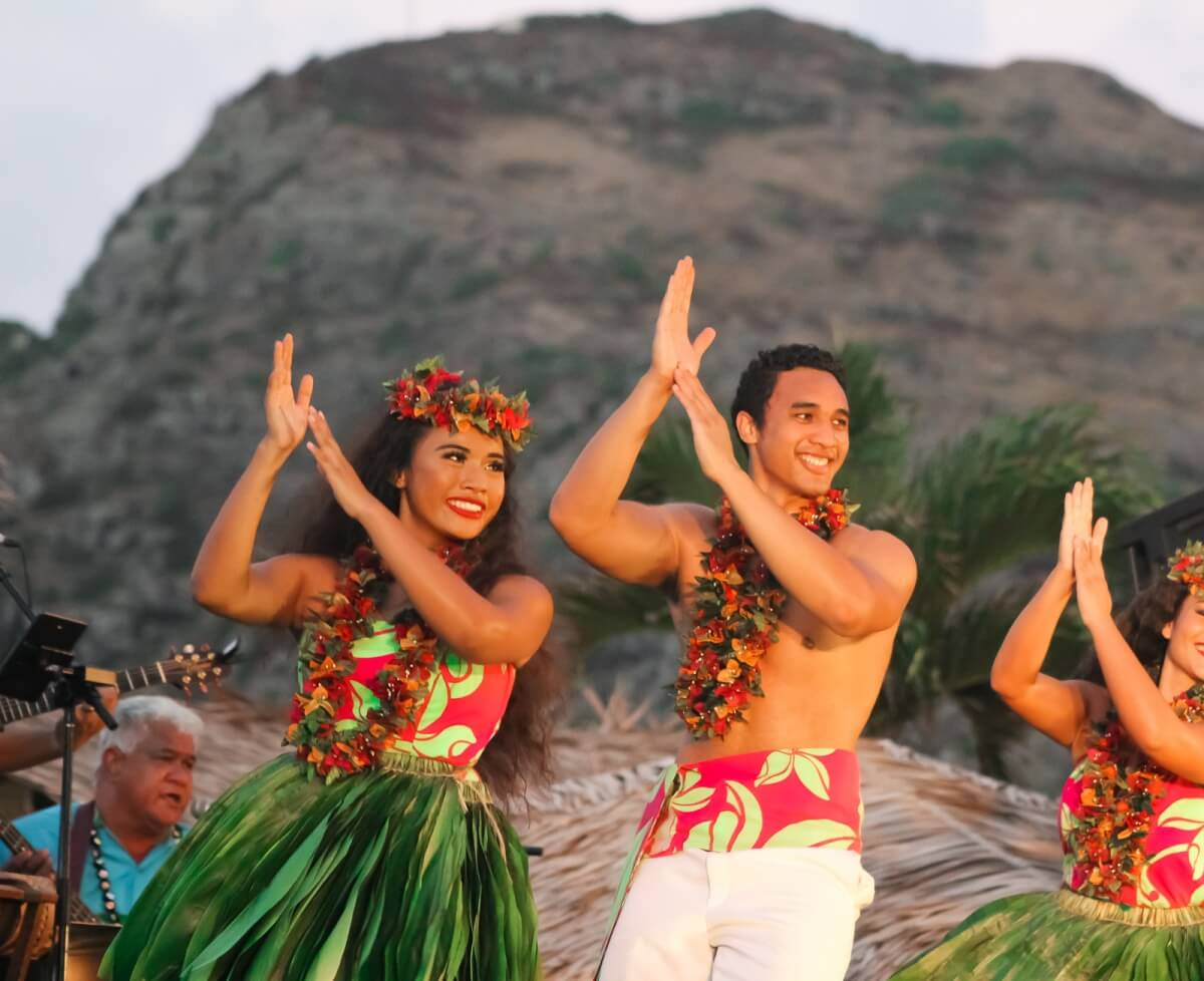 men and women in hawaii during a luau with traditional dress