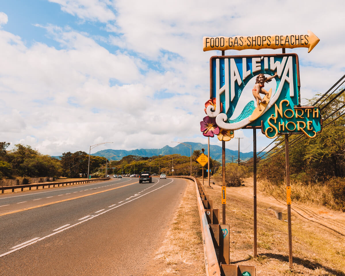 roadside sign for haleiwa north shore oahu hawaii with cars driving by