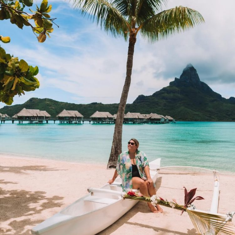 woman sitting on boat in bora bora at intercontinental bora bora resort and thalasso spa with palm tree in the center of the frame and beautiful white sand beach in the front with overwater bungalows and bora bora's famous mount otemanu in the backdrop bora bora vs moorea